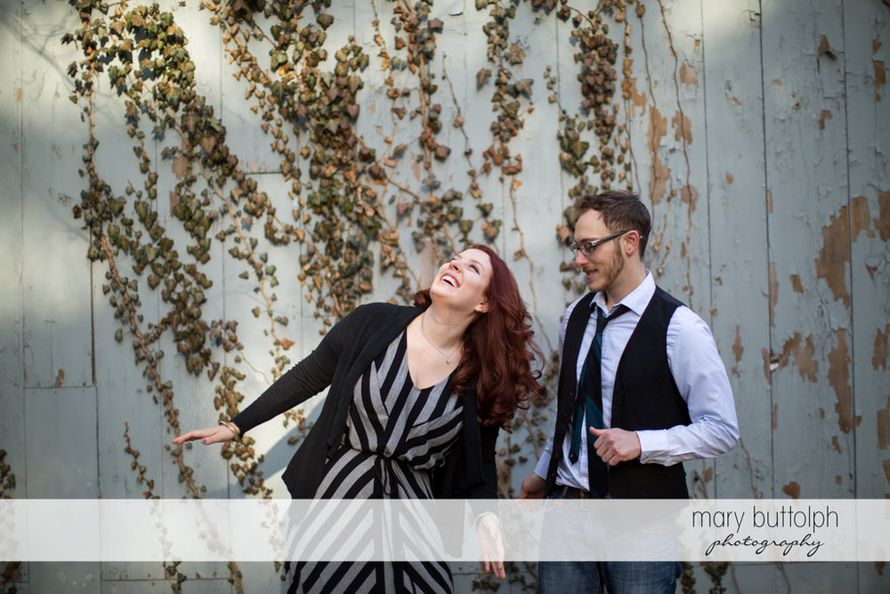 Couple stand next to a wooden wall at Skaneateles Engagement