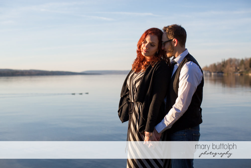 Couple pose near the calm waters of the lake at Skaneateles Engagement