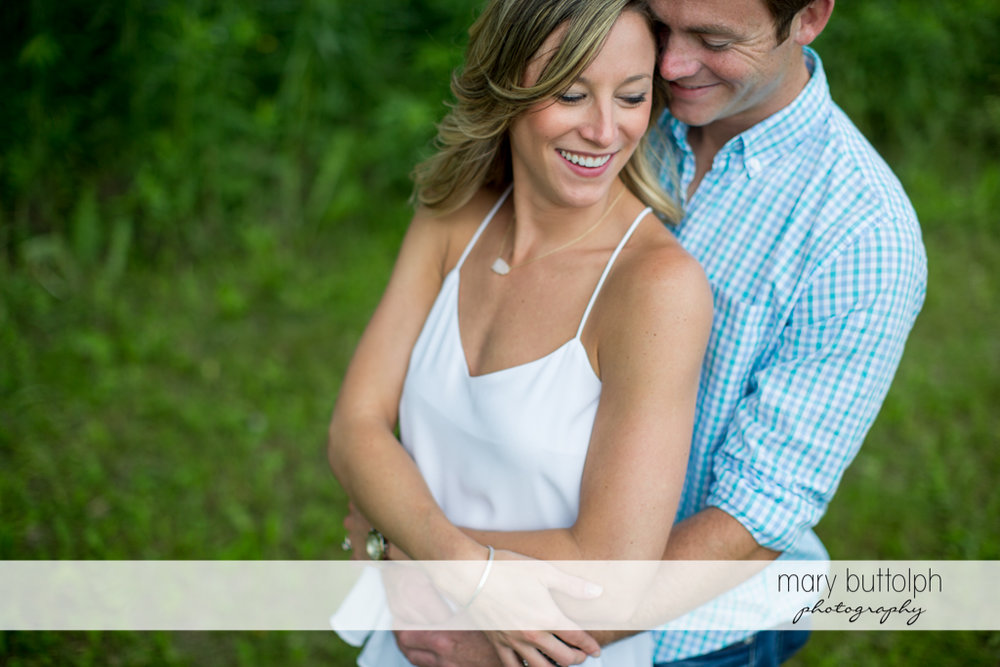 Couple cuddle up in the park at Skaneateles Engagement