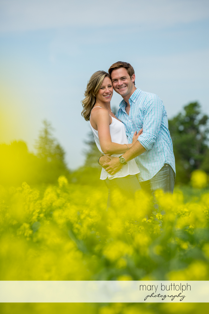 Couple embrace in front of flowers at Skaneateles Engagement