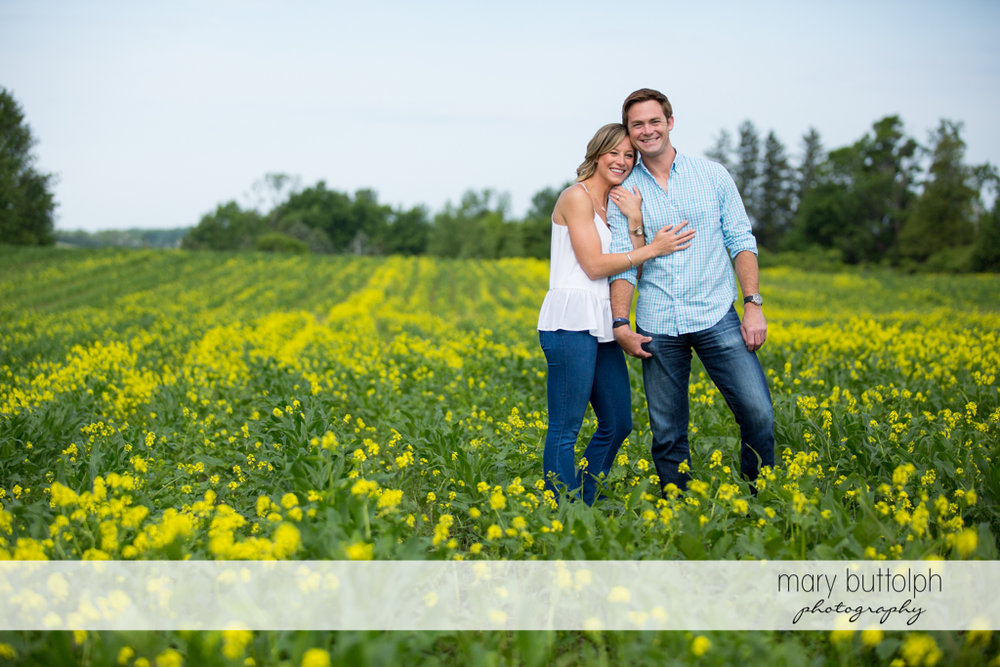 Couple pose in a garden full of flowers at Skaneateles Engagement