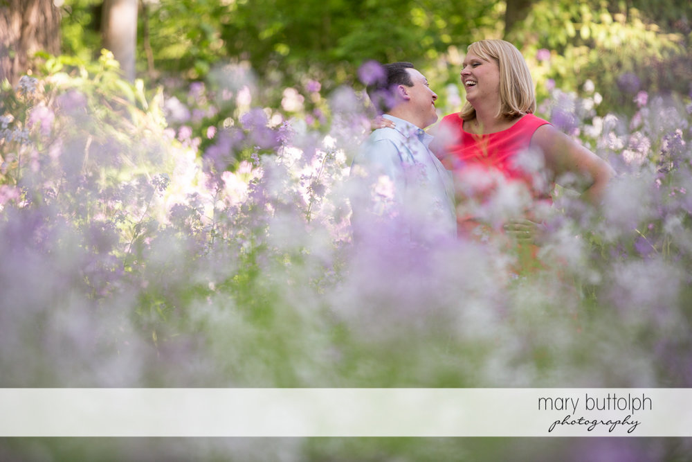 Couple surrounded by flowers at Skaneateles Lake Engagement