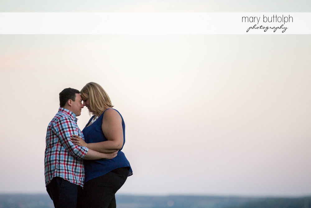 Couple hug by the lakeside at Skaneateles Lake Engagement