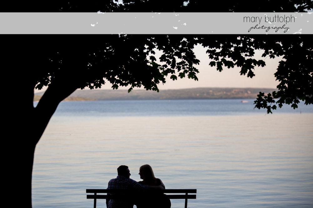 Couple relax by the lake at Skaneateles Lake Engagement