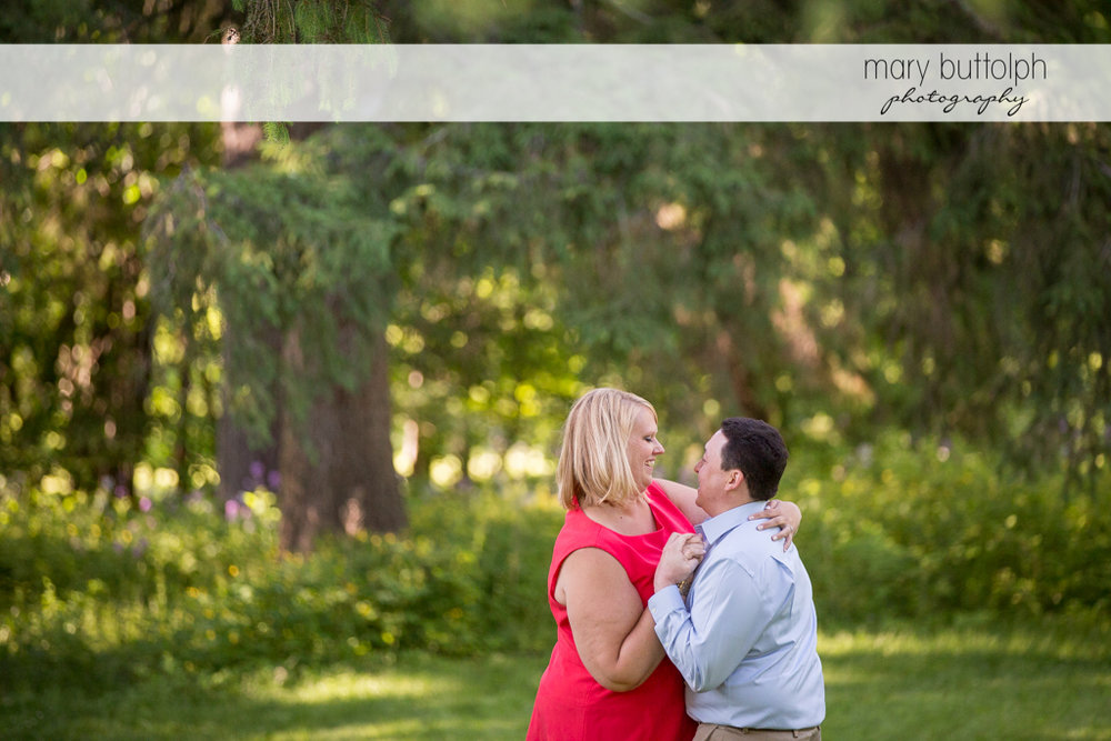Couple share a tender moment in the park at Skaneateles Lake Engagement