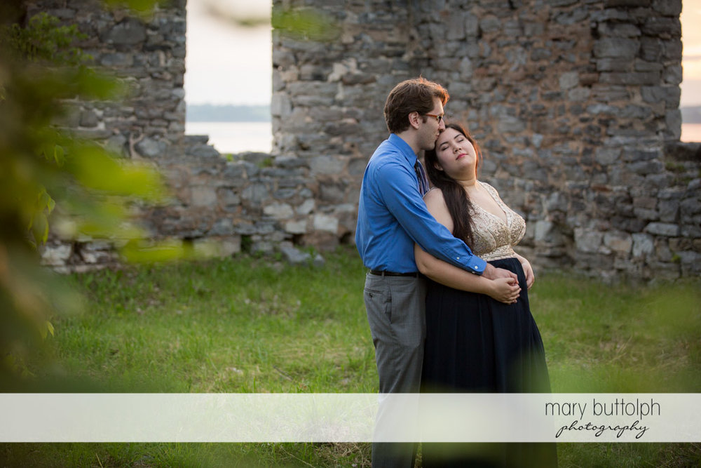 Couple cuddle up in front of a brick wall at Aurora Inn Engagement