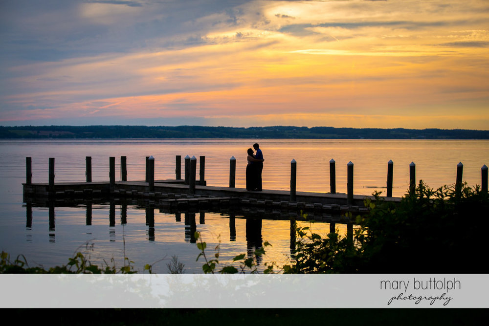 Couple show affection by the lake as the sun sets at Aurora Inn Engagement