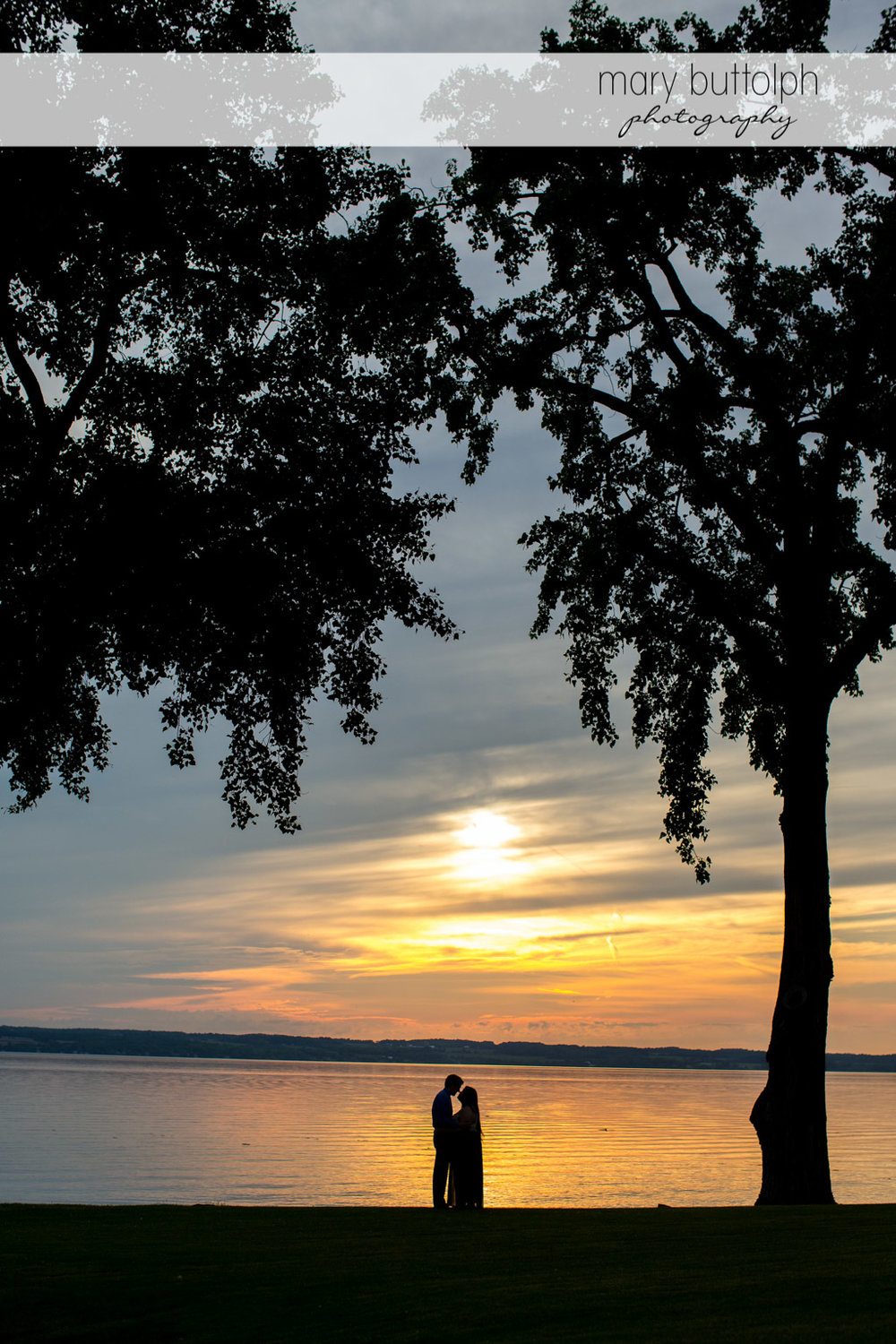 Couple in a dramatic shot by the lake as the sun sets at Aurora Inn Engagement