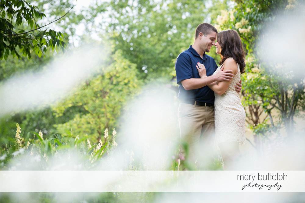 Couple in garden with flowers in the foreground at Skaneateles Engagement