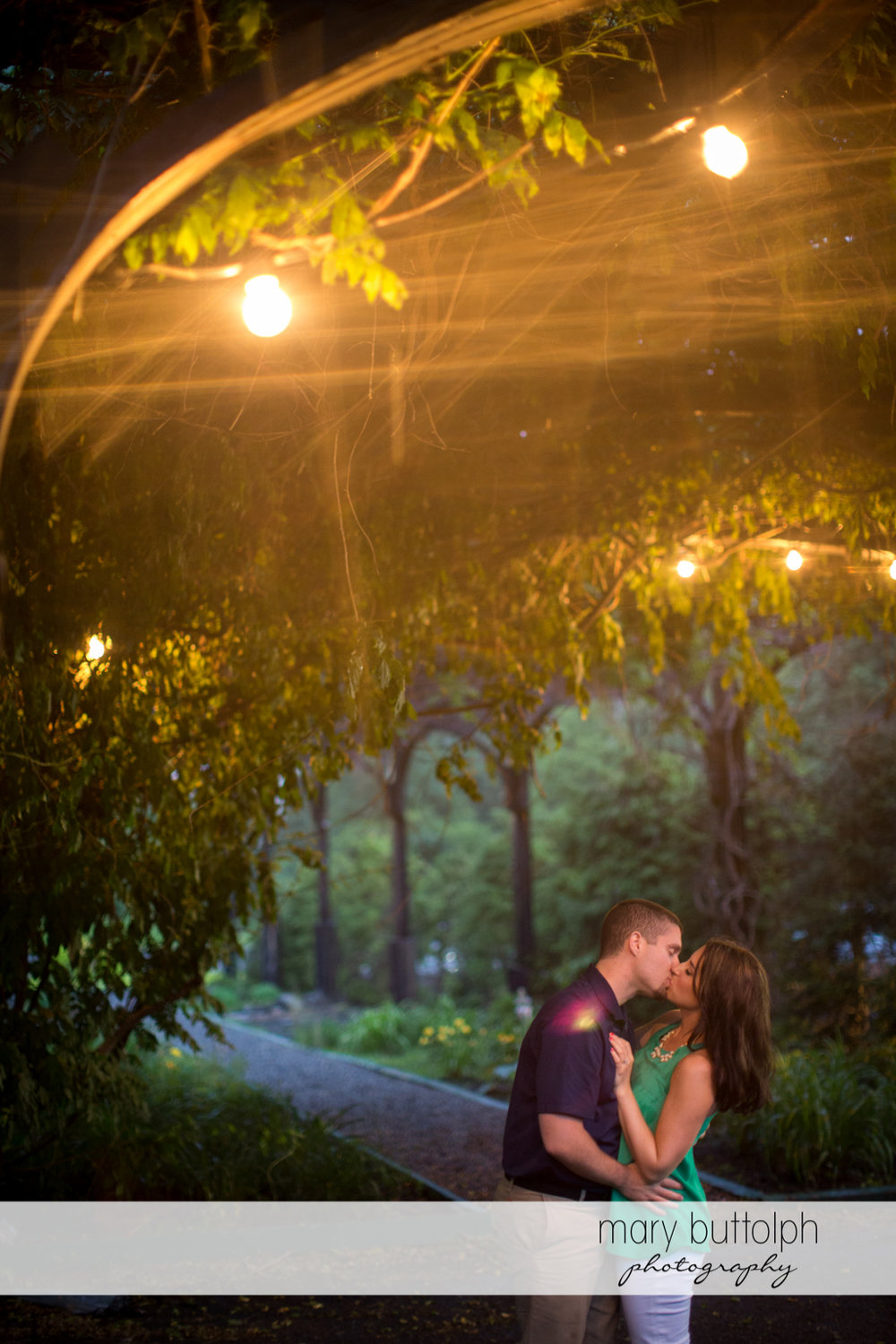 Couple kiss in the shade of trees in the garden at Skaneateles Engagement