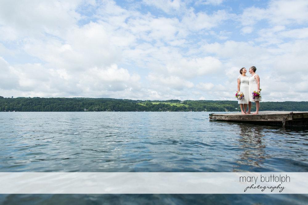 Same sex couple pose by the lake at Mandana Barn Wedding