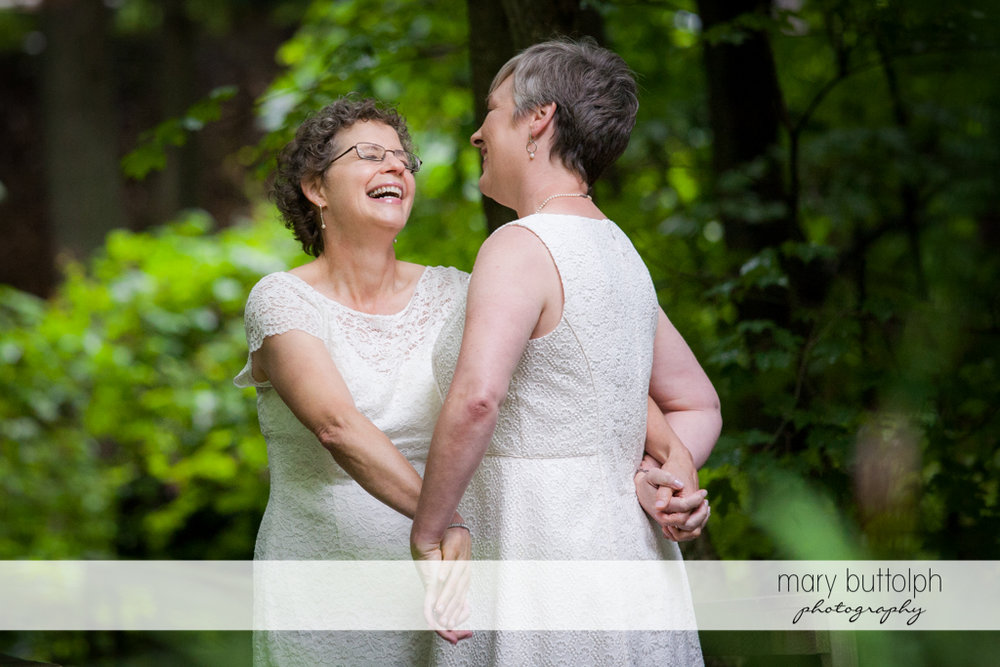 Same sex couple laugh in the woods while holding hands at Mandana Barn Wedding