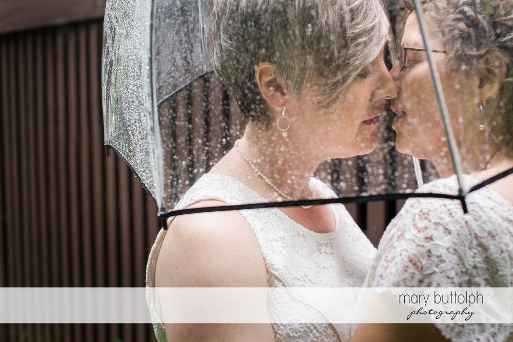 Same sex couple kiss in the rain at Mandana Barn Wedding