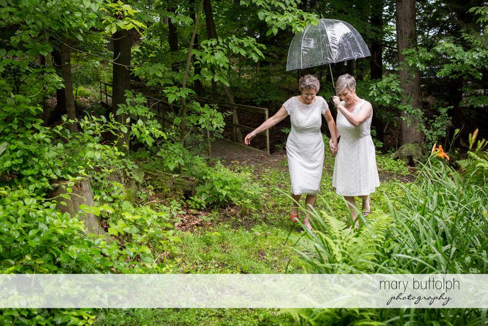 Same sex couple take a walk in the woods at Mandana Barn Wedding