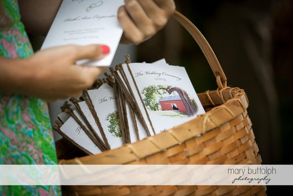 A basket holds the wedding program at Mandana Barn Wedding