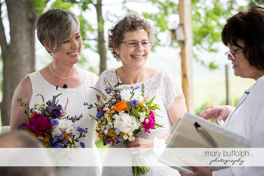 Same sex couple face the marriage officiant at Mandana Barn Wedding