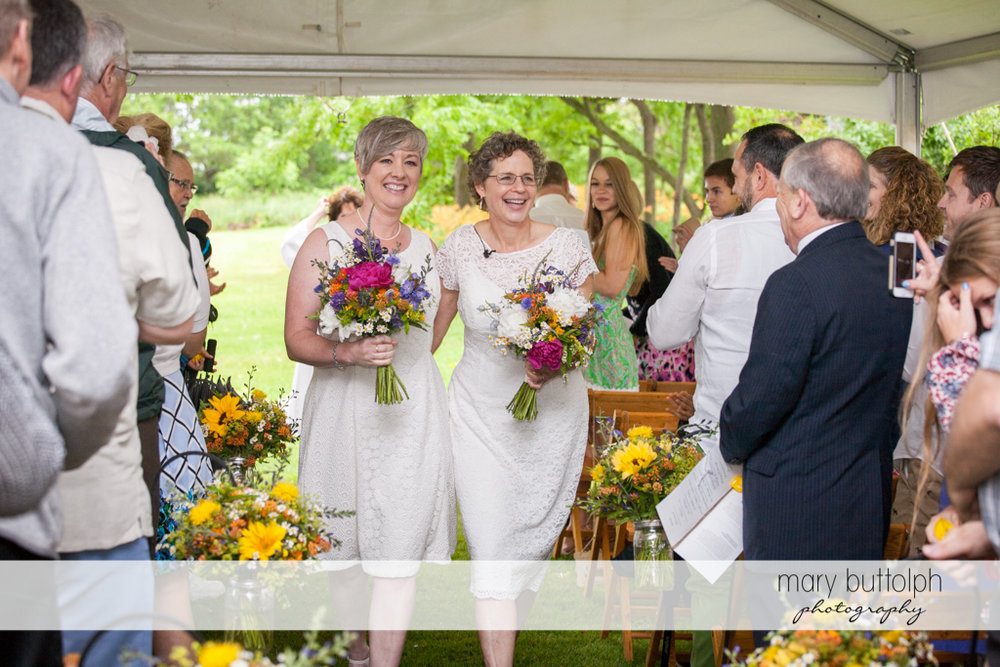 Same sex couple with flowers leave the wedding tent at Mandana Barn Wedding