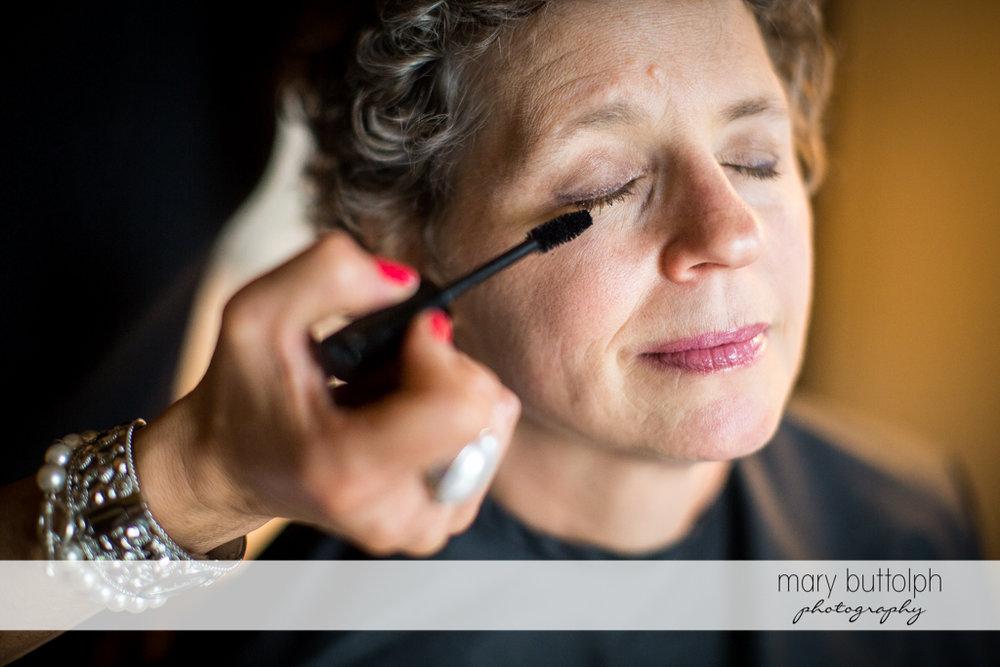 Makeup artist applies mascara to the bride's eyelashes at Mandana Barn Wedding