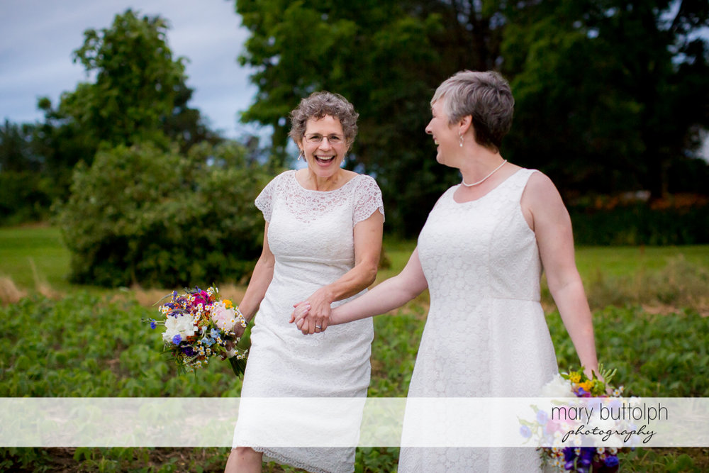 Same sex couple hold hands while strolling in the field at Mandana Barn Wedding