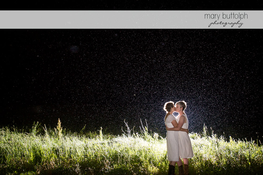 Couple kiss in the moonlight in the field at Mandana Barn Wedding
