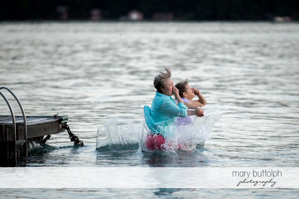 Same sex couple dive in the lake at Mandana Barn Wedding