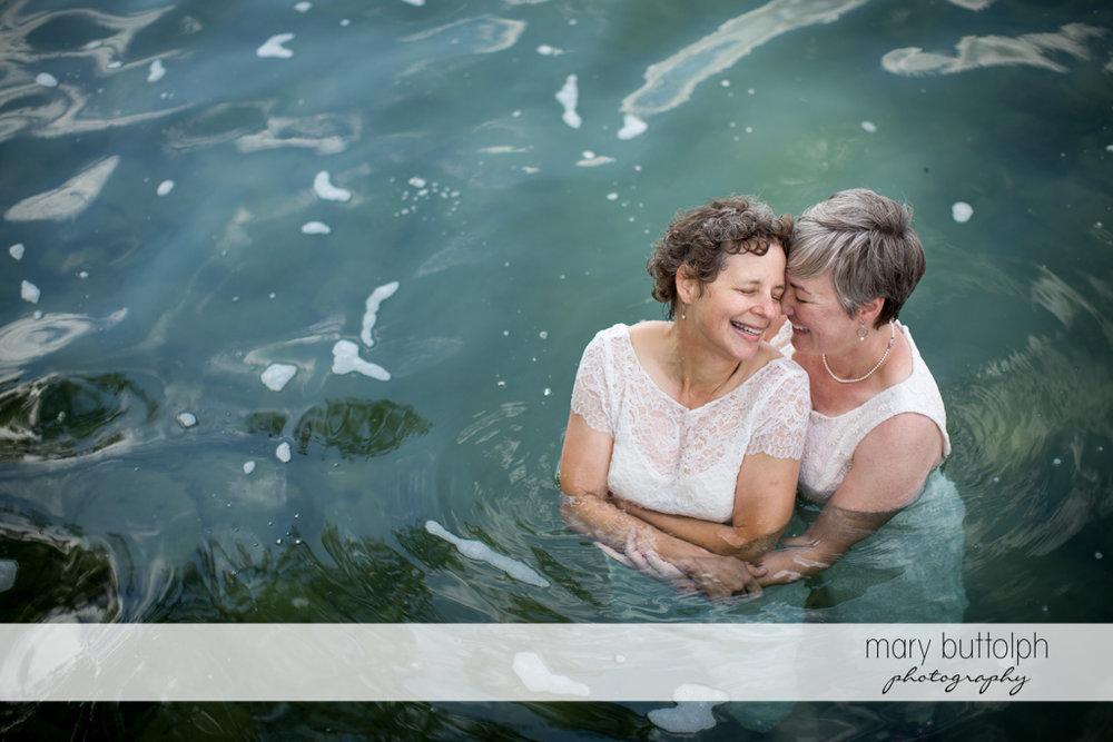 Same sex couple take a dip in the lake at Mandana Barn Wedding