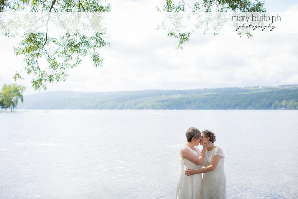 Same sex couple kiss in the lake at Mandana Barn Wedding