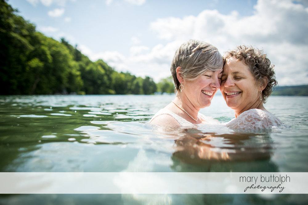 Same sex couple get cozy in the lake at Mandana Barn Wedding