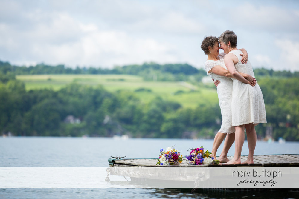 Same sex couple rub noses near the lake at Mandana Barn Wedding