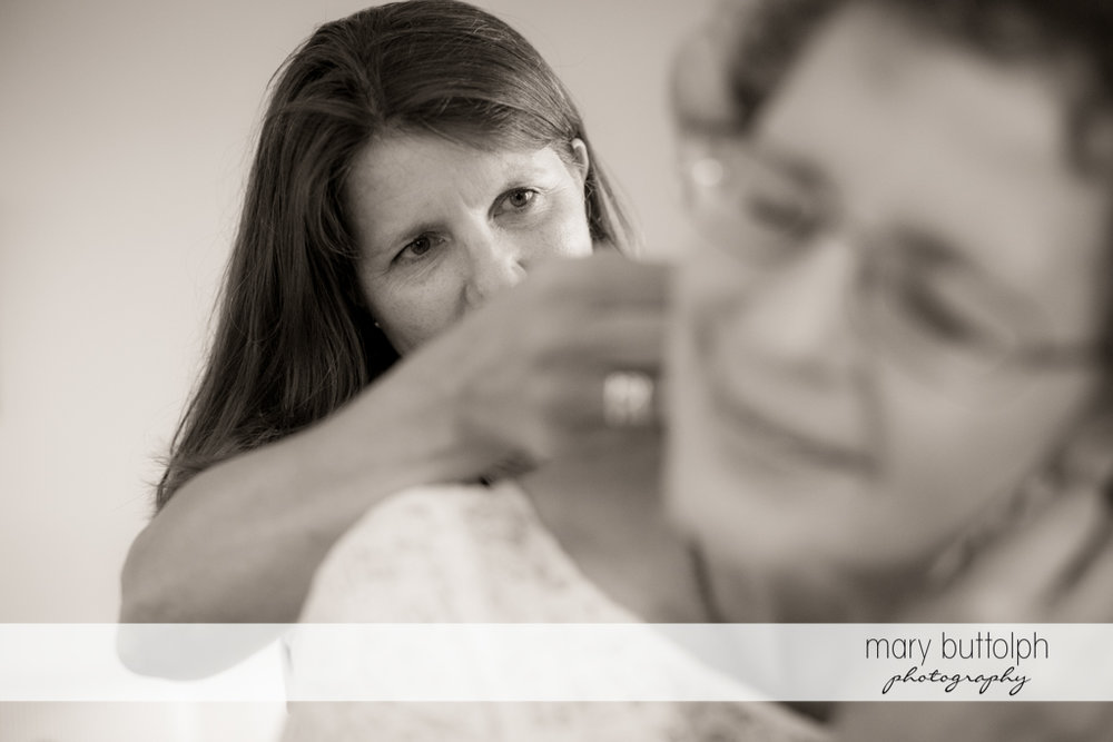 A friend fixes one of the bride's earings at Mandana Barn Wedding