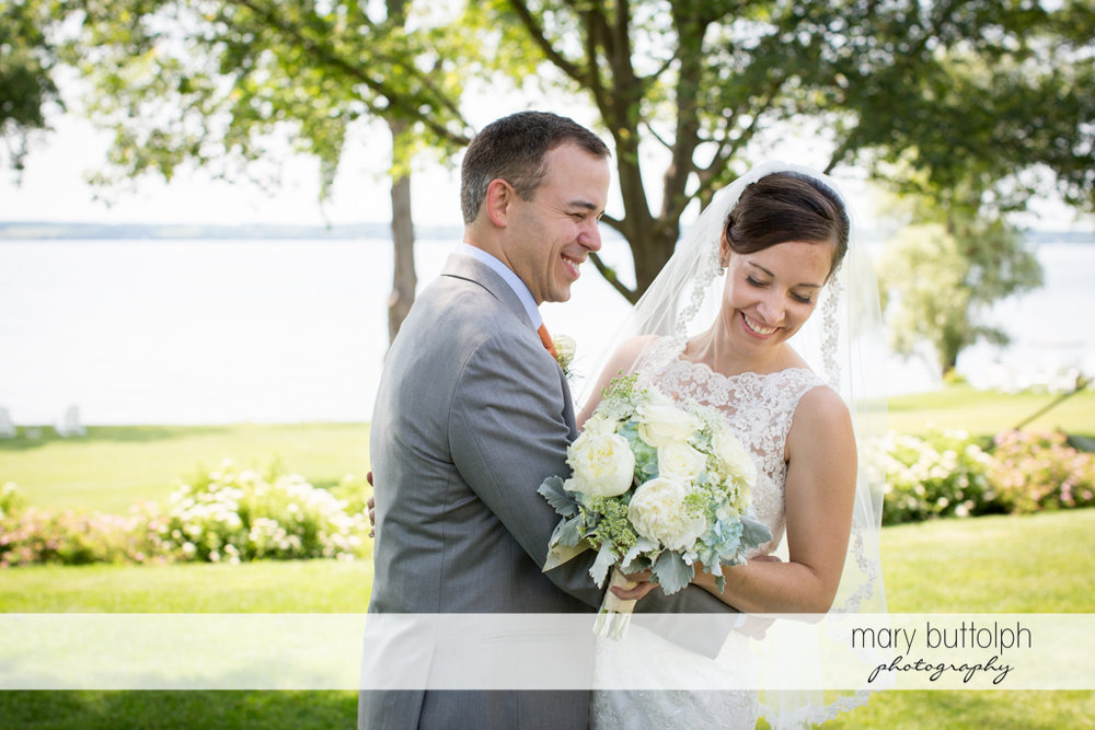 Couple share a tender moment in the garden by the lake at the Inns of Aurora Wedding