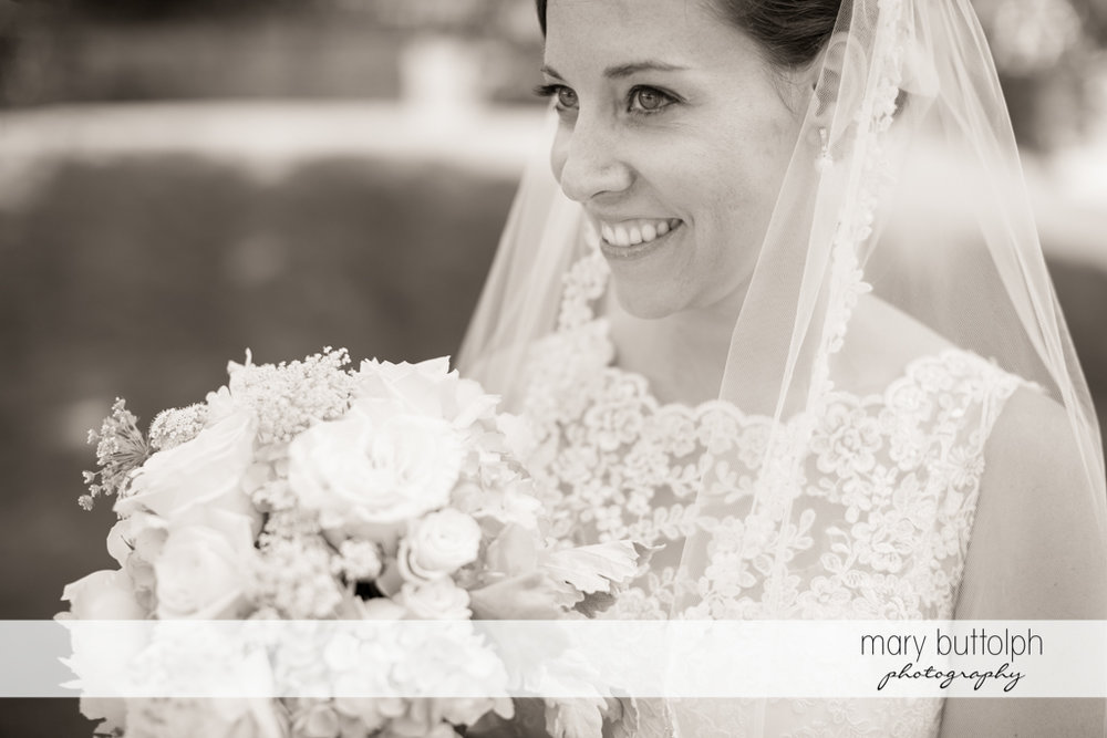 Close up shot of the happy bride holding a bouquet at the Inns of Aurora Wedding