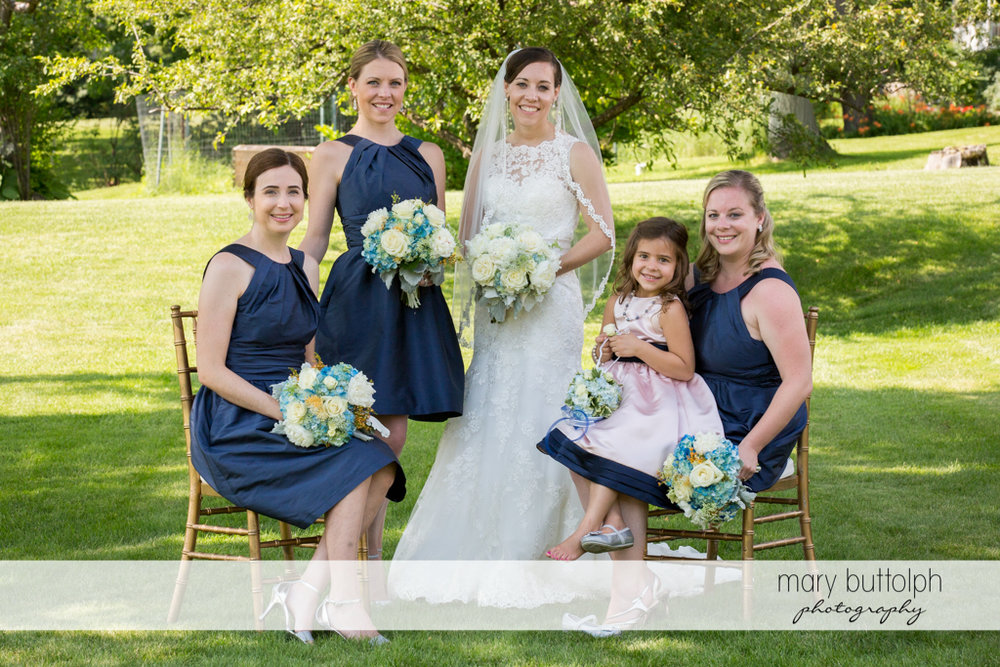 Bride and bridesmaids pose in the garden at the Inns of Aurora Wedding