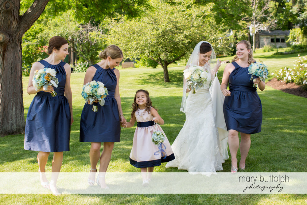 Bride and bridesmaids share a happy moment in the garden at the Inns of Aurora Wedding