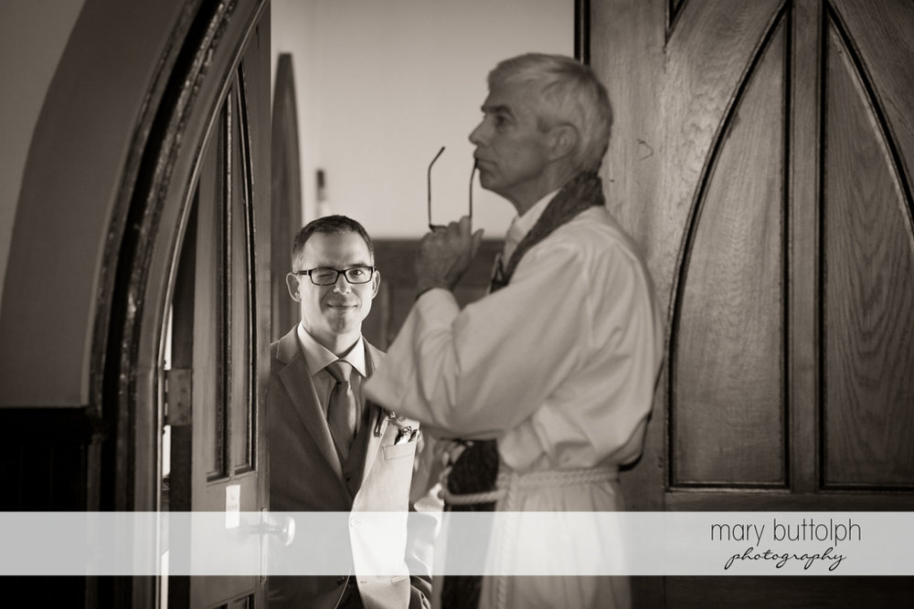 Groom blinks at the camera as the priest waits for the bride at the Inns of Aurora Wedding