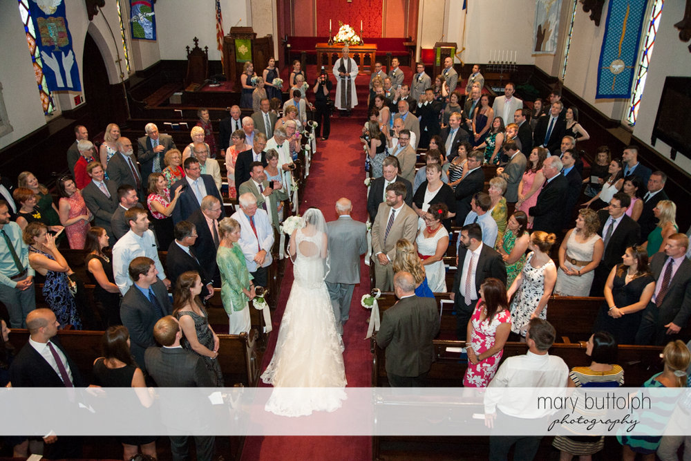 Guests watch the bride and her dad walk down the aisle at the Inns of Aurora Wedding