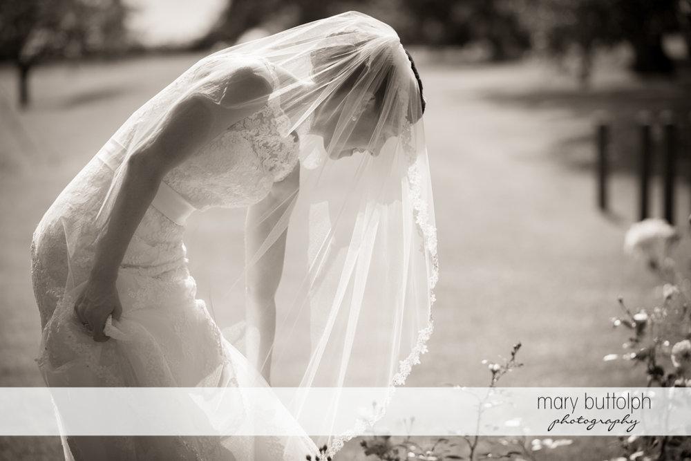 Bride picks a flower in the garden at the Inns of Aurora Wedding