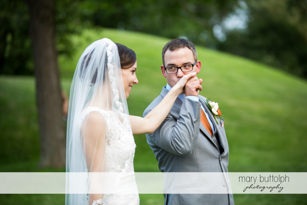 Groom kisses the bride's hand in the garden at the Inns of Aurora Wedding