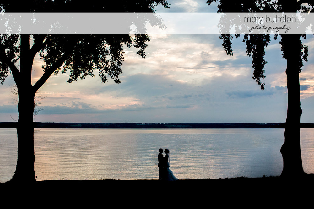 Couple catch the last rays of the sun near the lake at the Inns of Aurora Wedding