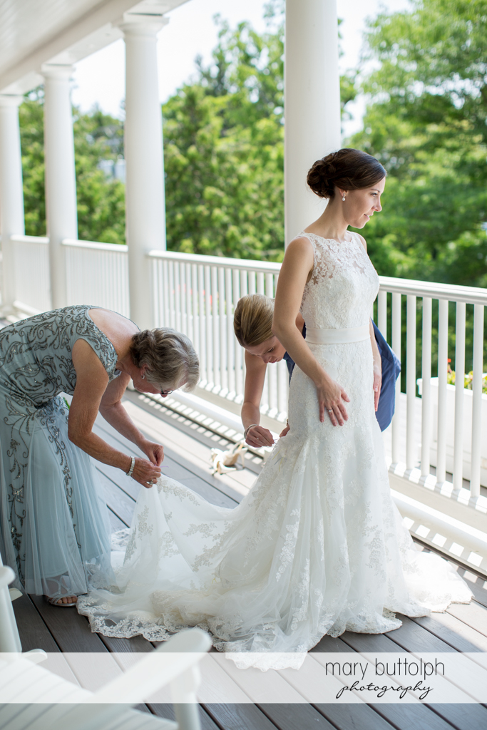 Relatives adjust the bride's wedding dress on the porch at the Inns of Aurora Wedding
