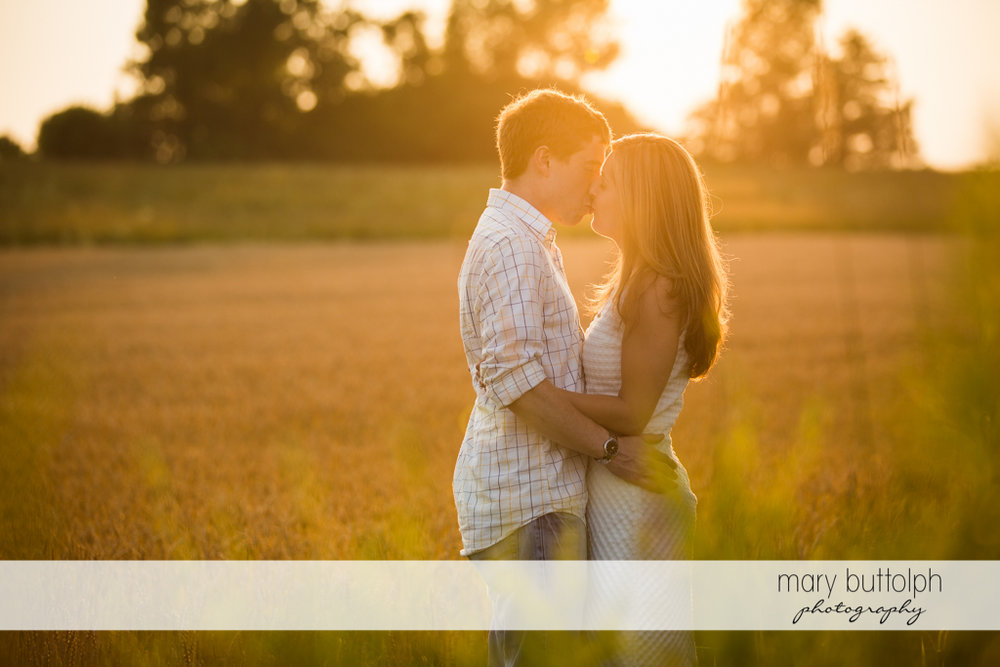 Couple hold each other as the sun sets at Skaneateles Engagement