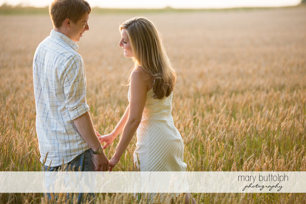 Couple stand in front of a wheat field at Skaneateles Engagement