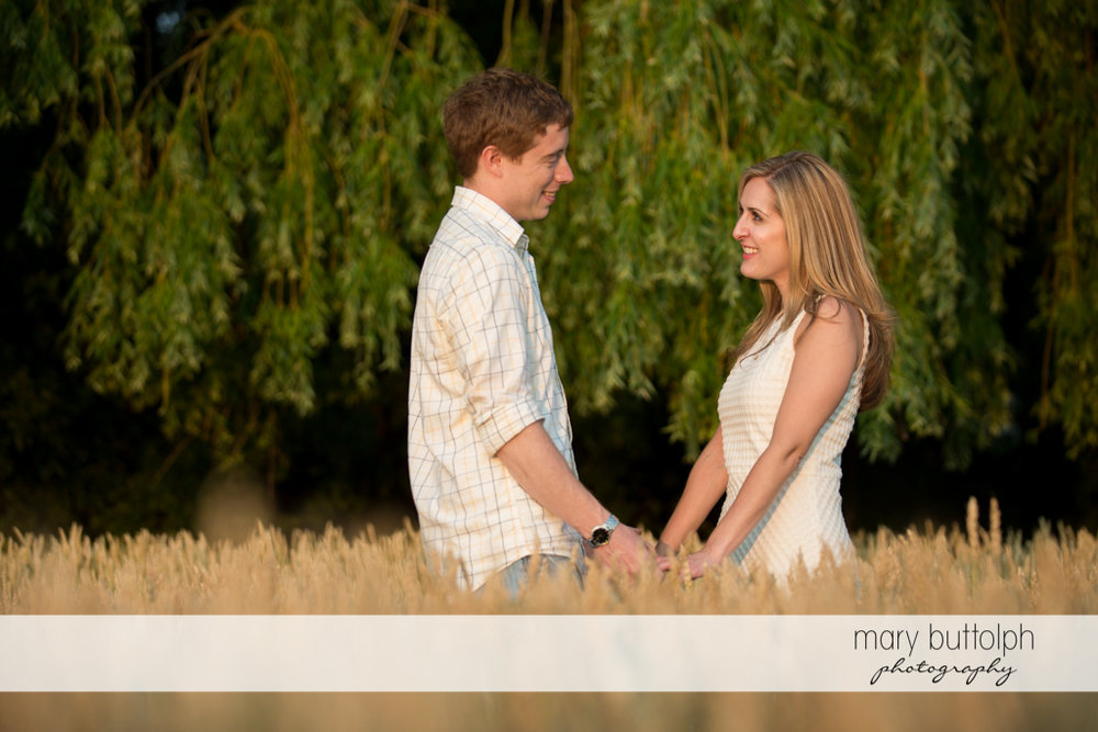 Couple hold hands in the middle of a wheat field at Skaneateles Engagement