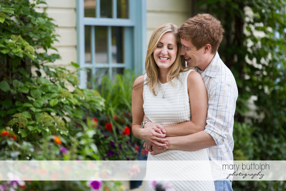 Couple embrace in front of a house at Skaneateles Engagement