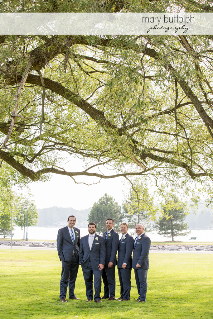 Groom and groomsmen pose under a tree in the garden at Emerson Park Pavilion Wedding