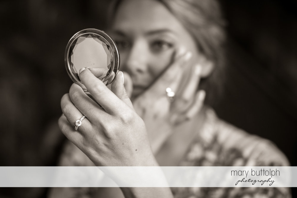 Bride checking her makeup with a small mirror at Emerson Park Pavilion Wedding