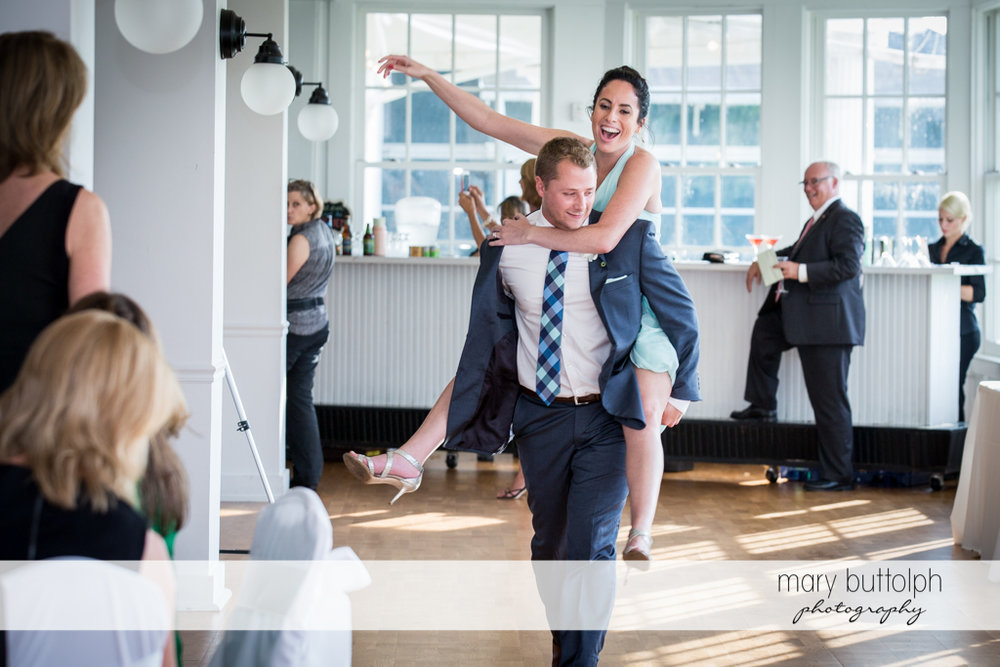 Man gives woman a piggyback ride at Emerson Park Pavilion Wedding