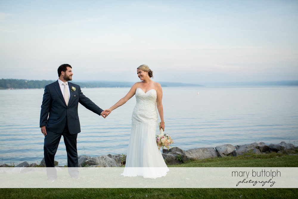 Couple hold hands by the lake at Emerson Park Pavilion Wedding