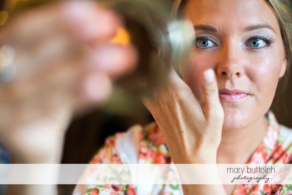 Bride checks her eye makeup at Emerson Park Pavilion Wedding