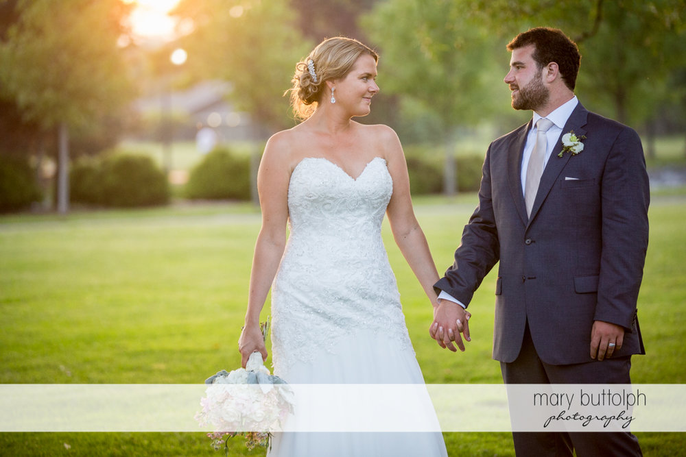 Couple holds hands in the garden at Emerson Park Pavilion Wedding